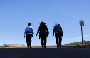 Women walk together up a hill as they participate in some morning exercise during a visit to Torrey Pines State Park in San Diego